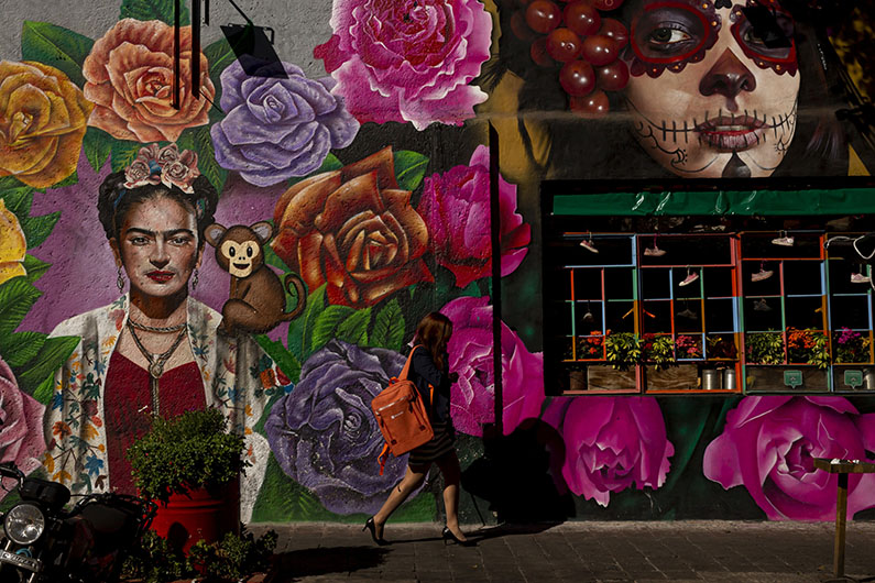 A pedestrians walks in front of a building with a mural painted on it.