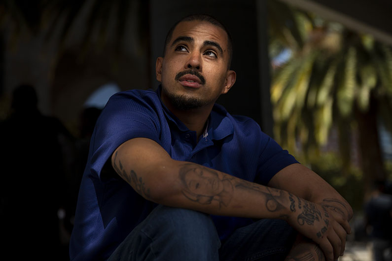Rogelio Hernandez talks outside a call center in Mexico City, Mexico. He has tattoos on his arms.