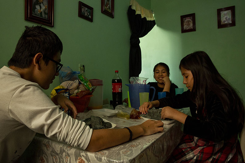 Josue Zarazua's children — from left, Jared, 14, Ayleen, 11, and Paulina, 10 — eat lunch in their Mexico City apartment.