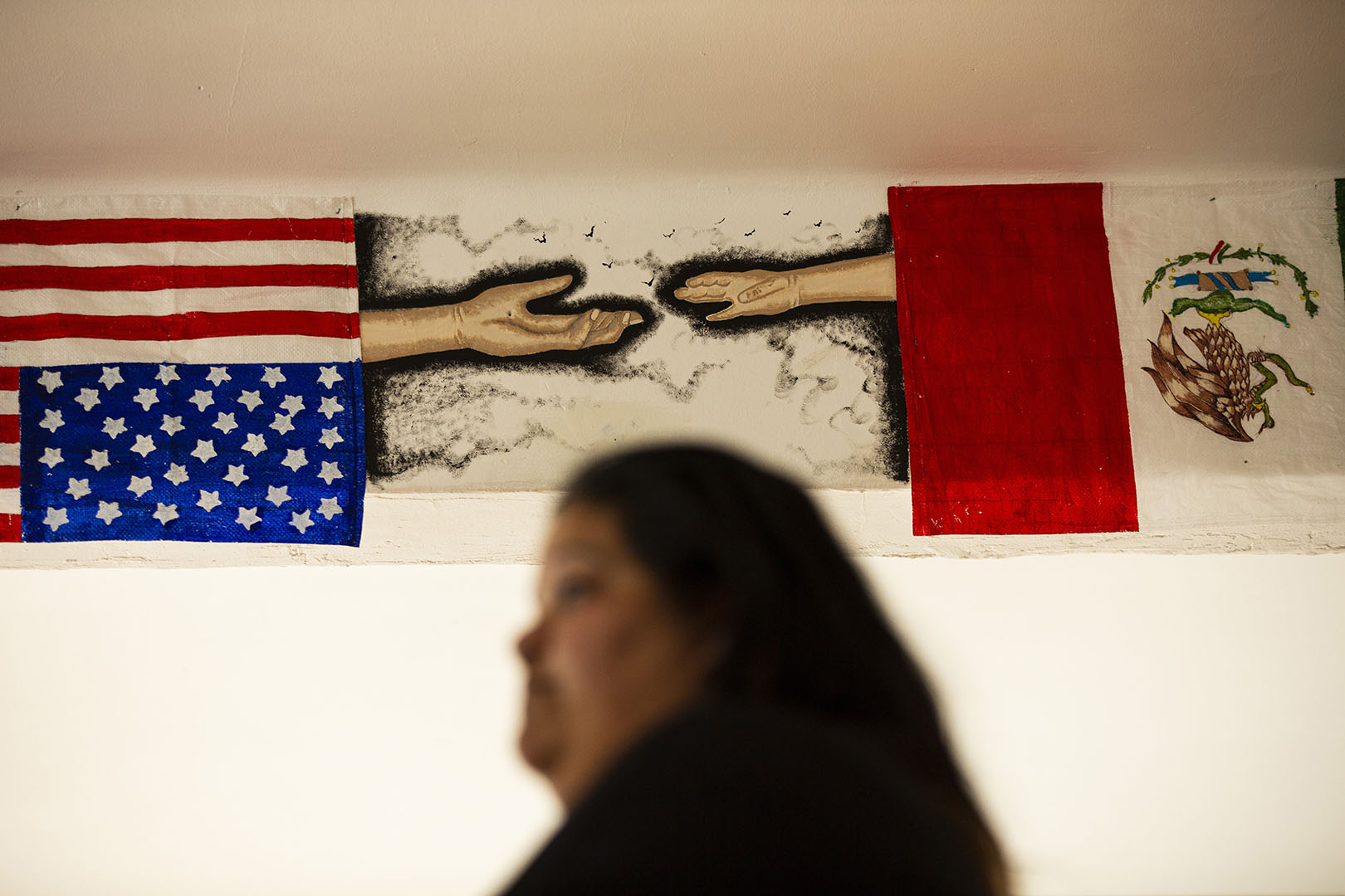 Maggie Loredo, a co-founder and co-director at Poch@ House, talks to a group in their Mexico City space. A piece of art depicting the U.S and Mexico flags hangs on the wall.