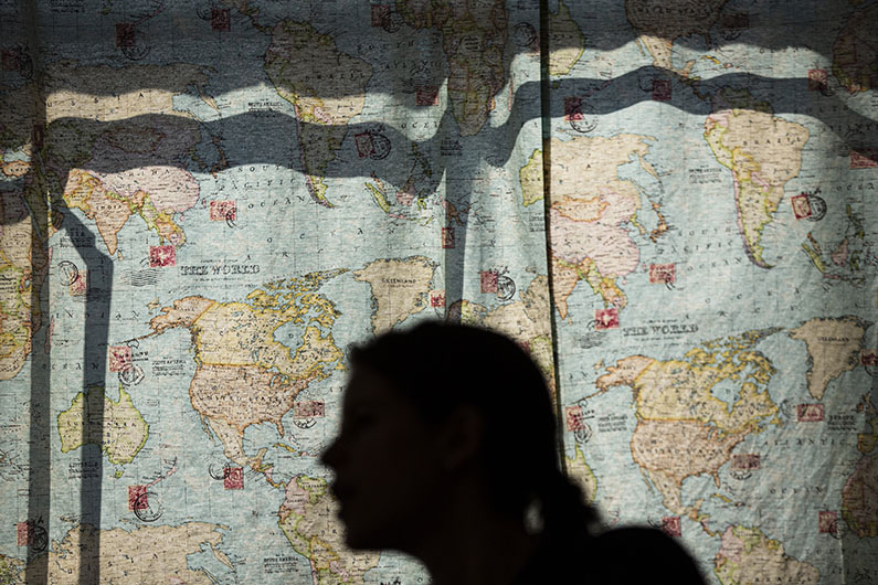 A shadow of a person is cast on a large world map at Poch@ House.