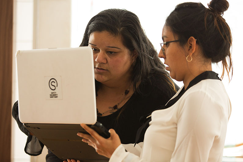 Poch@ House's Maggie Loredo, left, and Ximena Ortiz, right, look at a résumé on a laptop computer.