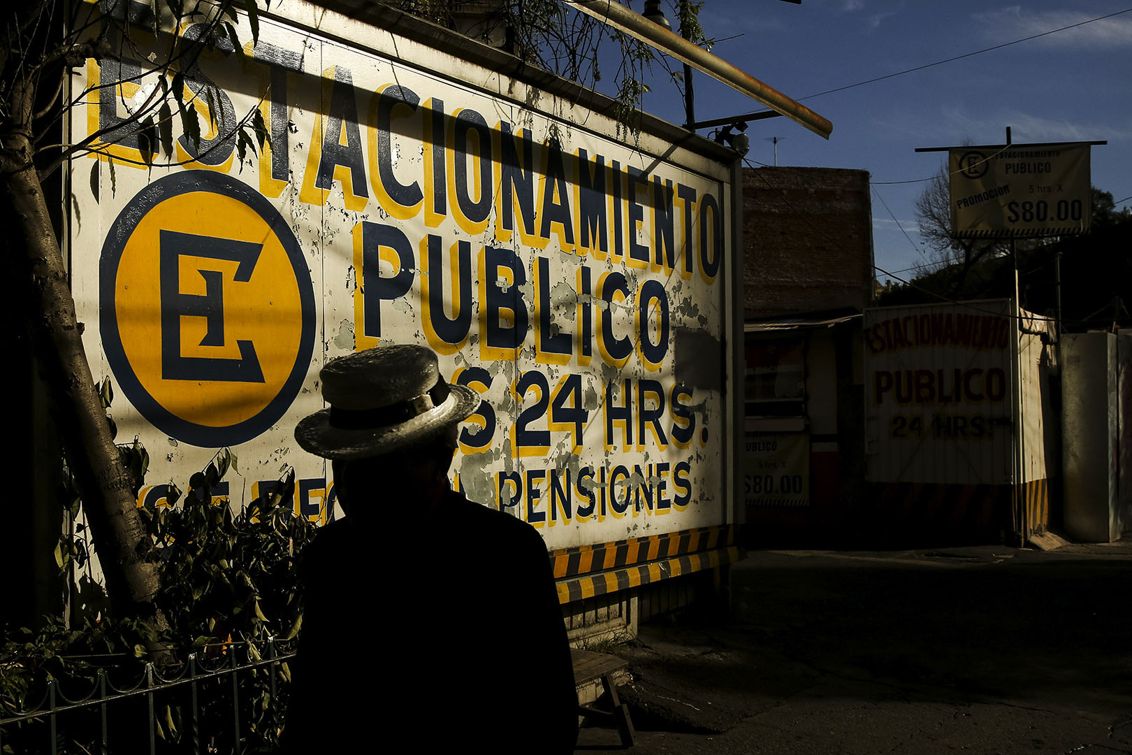 A person wearing a hat walks in front of a large hand-painted sign in Mexico City.